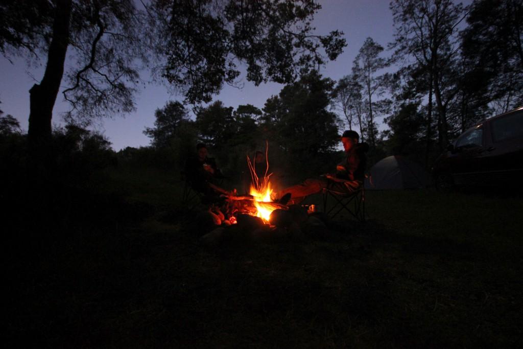 Jungs, ums Feuer sitzend.